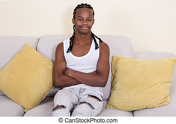 Young African-American man sitting on couch