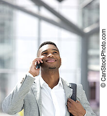 Young african american man smiling with mobile phone