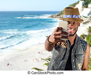 Young african american man taking selfie at the beach