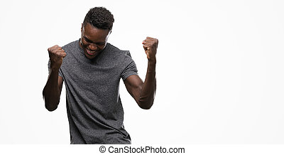 Young african american man wearing grey t-shirt very happy and excited doing winner gesture with arms raised, smiling and screaming for success. Celebration concept.