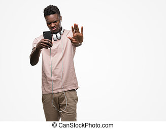 Young african american man wearing headphones and holding smartphone with open hand doing stop sign with serious and confident expression, defense gesture