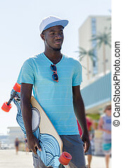 Young African American man with skateboard