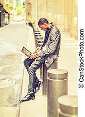 Young African American Man working on laptop computer on vintage street in New York