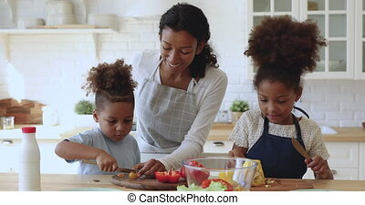 Young african american mom teaching little kids cutting fresh vegetables.