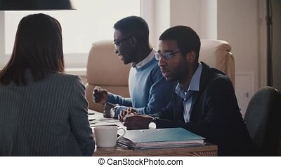 Young African American office worker talking to unrecognizable female business coach at team meeting slow motion.