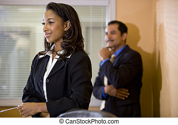 Young African-American office worker with manager in background