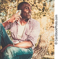 Young african american sitting on a tree with mobile phone