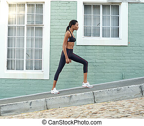 Young african american sports woman stretching legs