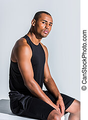 young african american sportsman sitting and looking at camera on grey