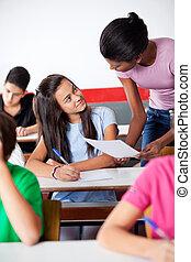 Young African American teacher assisting teenage schoolgirl...