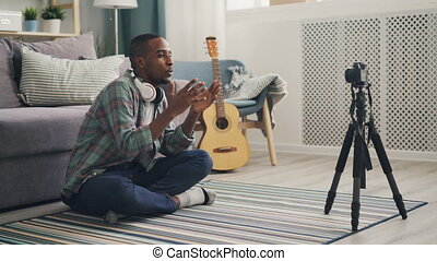 Young African American vlogger is recording video for...