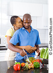 wife kissing husband in kitchen
