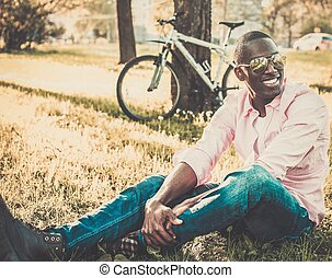 Young african american with bicycle in a park
