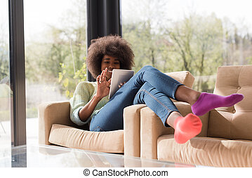 young african american woman at home using digital tablet