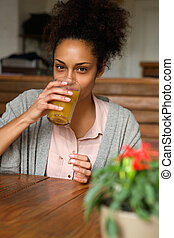 Young african american woman drinking orange juice