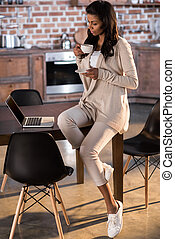 young african american woman drinking coffee and using laptop at kitchen