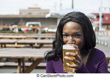 Young African American Woman Drinks Pint of Pale Ale