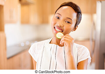 young african american woman eating a slice of cucumber