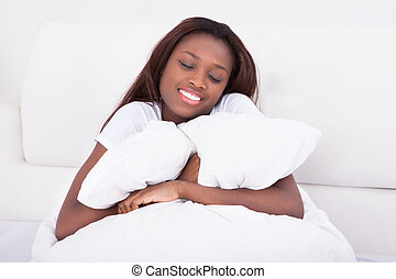 Young African American woman embracing blanket