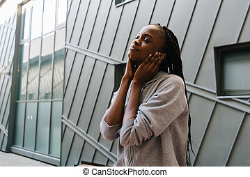 Young african american woman enjoying music with headphones and closed eyes