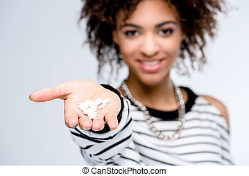 young african american woman giving drugs isolated on white