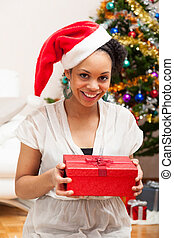 Young African American woman holding a gift box - Black people