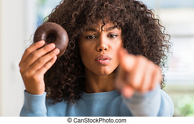 Young african american woman holding chocolate donut at home pointing with finger to the camera and to you, hand sign, positive and confident gesture from the front