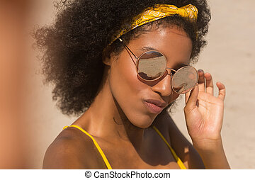 Young African American woman in yellow bikini and sunglasses looking at camera on beach