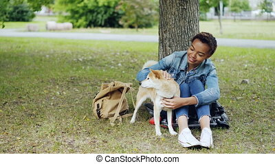 Young African American woman is caressing adorable puppy...
