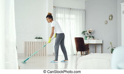 Young African American woman is cleaning floor in modern...