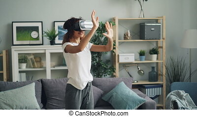 Young African American woman is enjoying experience with augmented reality glasses wearing modern vr headset. Slim girl is moving hands and head standing at home.