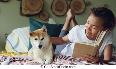 Young African American woman is reading book and caressing...
