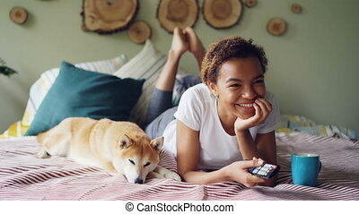 African American woman is watching TV holding remote control...