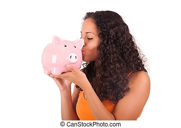 Young african american woman kissing piggy bank