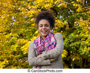 Young african american woman laughing outdoors in autumn