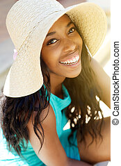 Young african american woman laughing with sun hat