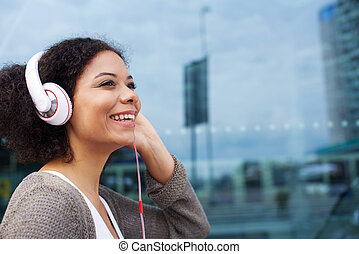 Young african american woman listening to music on headphones