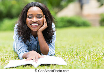 young african american woman lying on the grass