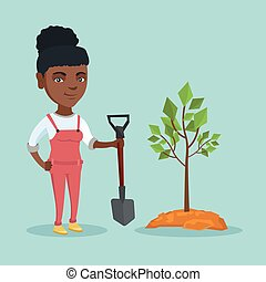 Young african-american woman planting a tree.