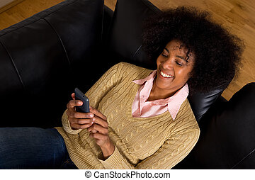 young african american woman reading her text messages at home