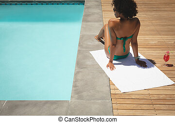 Young African American woman relaxing at poolside in her backyard