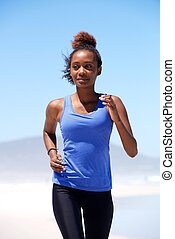 Young african american woman running at the beach