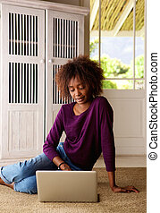 Young african american woman sitting at home with laptop
