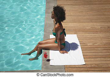 Young African American woman sitting at poolside in her backyard