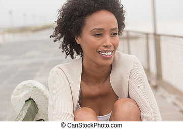 Young African American woman sitting on bench at promenade