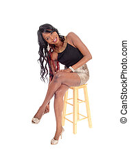 Young African American woman sitting on chair.