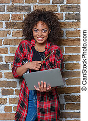 young african american woman smiling and holding laptop