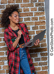 young african american woman smiling while using laptop and holding notebooks