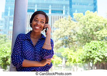 Young african american woman smiling with mobile phone