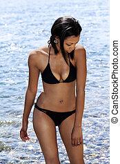 Young African American Woman Standing In Water Wearing Black Bikini
